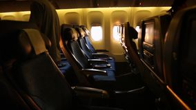 Airplane cabin with passengers boarding and sitting with a sunset light stock video