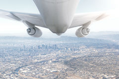 Airplane and cityscape. Peeking through clouds. 3D Rendering Royalty Free Stock Images