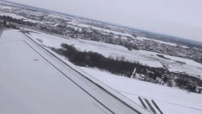 The airplane climbs over the airfield in overcast snowy weather stock video footage