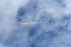 Airplane in clouds. Airplane flying in clouds over blue sky Stock Photos