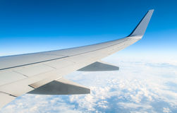 Airplane in clouds above earth Stock Image