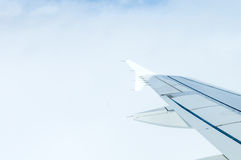 Airplane in clouds above earth Stock Photo