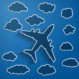 Airplane with clouds on a blue air background Stock Image