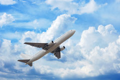 Airplane in cloudsape. Airplane in the sky full of fluffy clouds Royalty Free Stock Photo