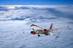 Airplane in cloudscape with sunset. Above clouds Stock Photography