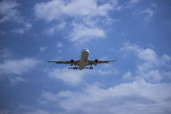 Airplane in the cloudy sky royalty free stock photo