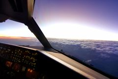 In airplane cockpit view, airplane flying over the cloud during sunset in the evening. royalty free stock photos