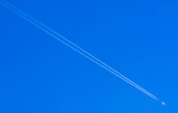 Airplane condensation trail going down on blue sky Stock Photos