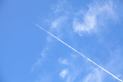 Airplane contrail against beautiful blue sky. Stock Photo