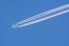 Airplane contrail. Closeup on airplane contrail against clear blue sky Royalty Free Stock Image