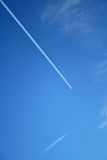 Airplane contrail in the sky. Airplain condensation trail in the cloudy sky, close to a military base Royalty Free Stock Photos