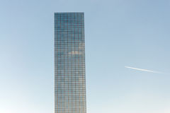 Airplane contrail and skyscrapers. Office Building against the sky and the high flying passenger plane with a contrail Stock Image