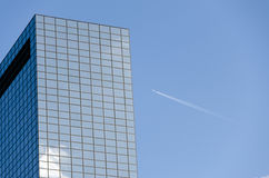 Airplane contrail and skyscrapers. Office Building against the sky and the high flying passenger plane with a contrail Stock Photo