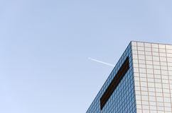 Airplane contrail and skyscrapers. Office Building against the sky and the high flying passenger plane with a contrail Royalty Free Stock Photo