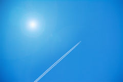 Airplane contrails under a shining sun Stock Photos