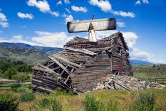 Airplane Crashed into Weathered Old Barn. Single Engine Airplane Crashed into a Weathered Old Barn Collapsing Under a Blue Sky in the Old West royalty free stock image