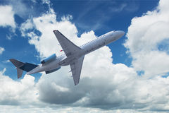Airplane with cumulus clouds Stock Images