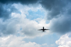 Airplane in the dark skies before storm, Transport concept. Royalty Free Stock Images