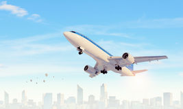 Airplane in day sky. Mixed media . Mixed media. Airliner flying above modern cityscape. Mixed media Royalty Free Stock Images