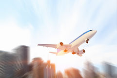 Airplane in day sky. Mixed media . Mixed media. Airliner flying above modern cityscape. Mixed media Stock Image