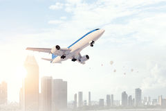 Airplane in day sky. Mixed media . Mixed media. Airliner flying above modern cityscape. Mixed media Stock Photo
