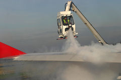 Airplane de-icing. Man de-icing the airplane's wing Royalty Free Stock Photo