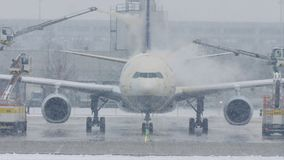 Airplane at deice pad, defrosting, Munich Airport. Winter with snow on runway