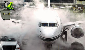 Airplane deicing from bucket horizontal. An airplane at the gate must be deiced before takeoff on a cold winter day Stock Image