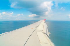 Airplane descending over a blue ocean to maldives island . Royalty Free Stock Image