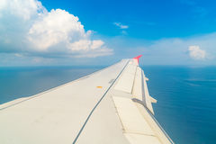Airplane descending over a blue ocean to maldives island . Royalty Free Stock Photography