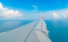 Airplane descending over a blue ocean to maldives island . Stock Image
