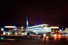 Airplane docked at the terminal. And ready for takeoff. Modern international airport at night stock photography