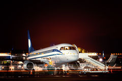 Airplane docked at the terminal. And ready for takeoff. Modern international airport at night stock photo