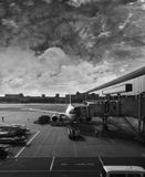 AIRPLANE DOCKING. AT AIRPORT IN CLOUDY DAY stock photos