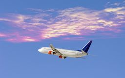 Airplane in dramatic sky. Airplane flying into setting sun royalty free stock photo