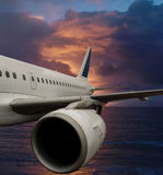 Airplane in dramatic sky over sea . Stock Photo