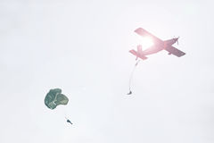 Airplane dropping off paratroopers stock photos