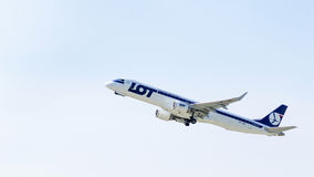 Airplane Embraer in the sky. Airplane in the sky. Embraer ERJ-195LR (SP-LNC) by LOT - Polish Airlines on the background of clear sky after take-off from airport Stock Photos