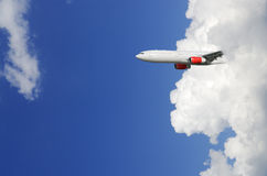 Airplane emerging from out of cloud Royalty Free Stock Images