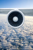 Airplane engine. And wings on the blue sky and white clouds stock image