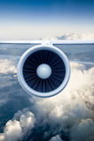 Airplane engine. And wings on the blue sky and white clouds stock photography