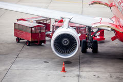 Airplane engine in front of loading luggage from airplane. In airport Royalty Free Stock Photos