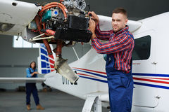 Airplane Engineers repairing Plane in Hangar. Airplane service team repairing plane in hangar:  modern mechanic fixing disassembled airplane turbine and looking Royalty Free Stock Images