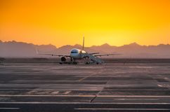 Airplane in the Evening Against the Backdrop of the Mountains Royalty Free Stock Photography
