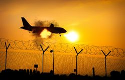 Airplane on fire in midair close to ground - digital manipulation.  stock photos