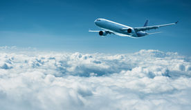 Airplane flies above clouds - air travel. Passenger plane flies above the clouds - air travel Royalty Free Stock Image