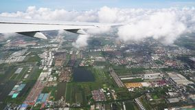 The airplane flies through the clouds above the earth, city roads and rooftops are visible below stock video