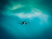 Airplane flies into the dramatic stormy clouds. Bad conditions for flight. Dangerous and risky aircraft transportation.  Stock Photos