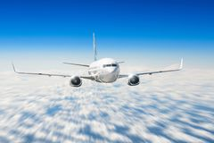 Airplane flies high in the sky above the clouds, with the effect of speed. Royalty Free Stock Images
