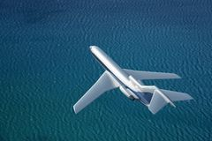 Airplane flies over a sea Royalty Free Stock Images
